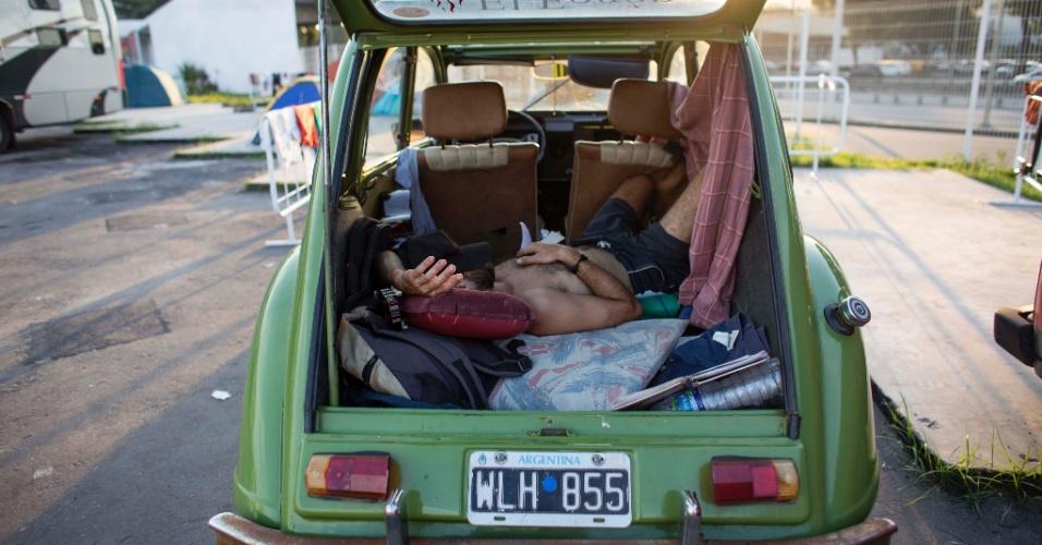 Torcedor descansa em carro com as placas da Argentina estacionado no sambódromo do Rio de Janeiro, locado para desafogar a concentração de pessoas abrigadas nas praias de Copacabana e Ipanema