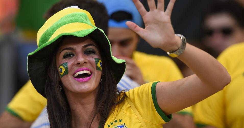 Torcedora do Brasil acena enquanto assiste ao jogo contra o Chile no Mineirão