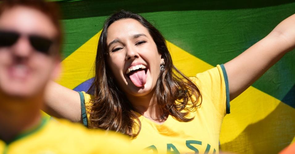 Torcedora exibe a bandeira e a língua na arquibancada do Mineirão antes do jogo contra o Chile