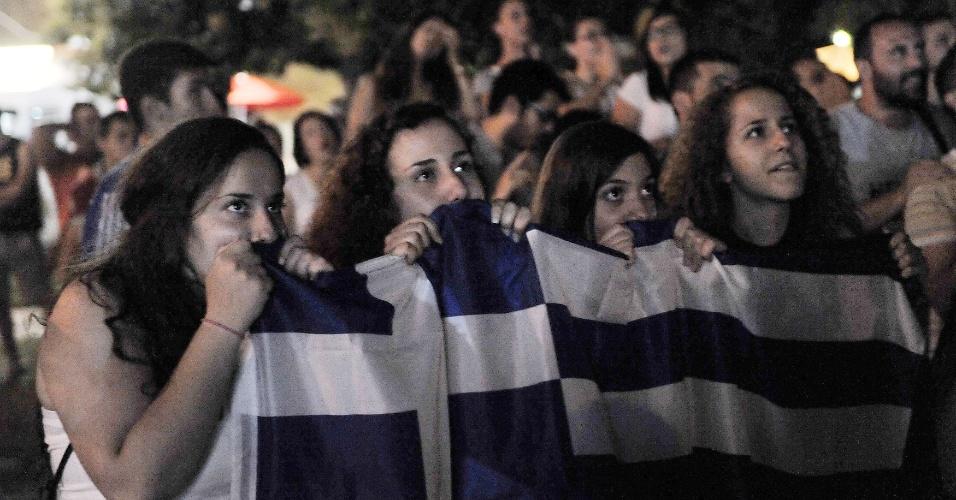 29.jun.2014 - Em Tessalônica, torcedoras gregas ficam tensas atrás de bandeira durante partida da seleção nacional contra a Costa Rica pelas oitavas da Copa do Mundo
