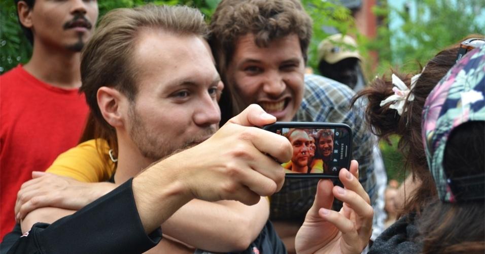 Casal de alemães tira selfie com amigo brasileiro durante festa junina que exibiu jogo do Brasil neste sábado