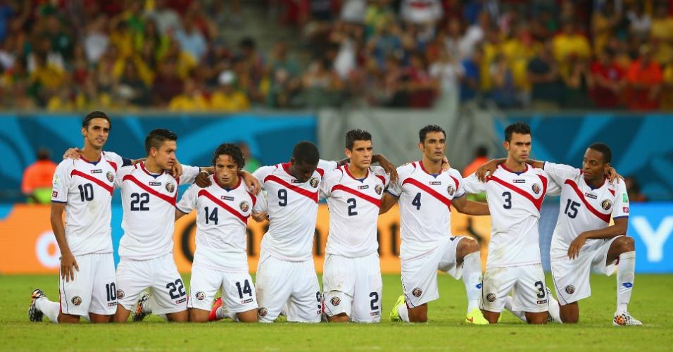 Jogadores da Costa Rica ficam abraçados no centro do campo durante a decisão por pênaltis contra a Grécia