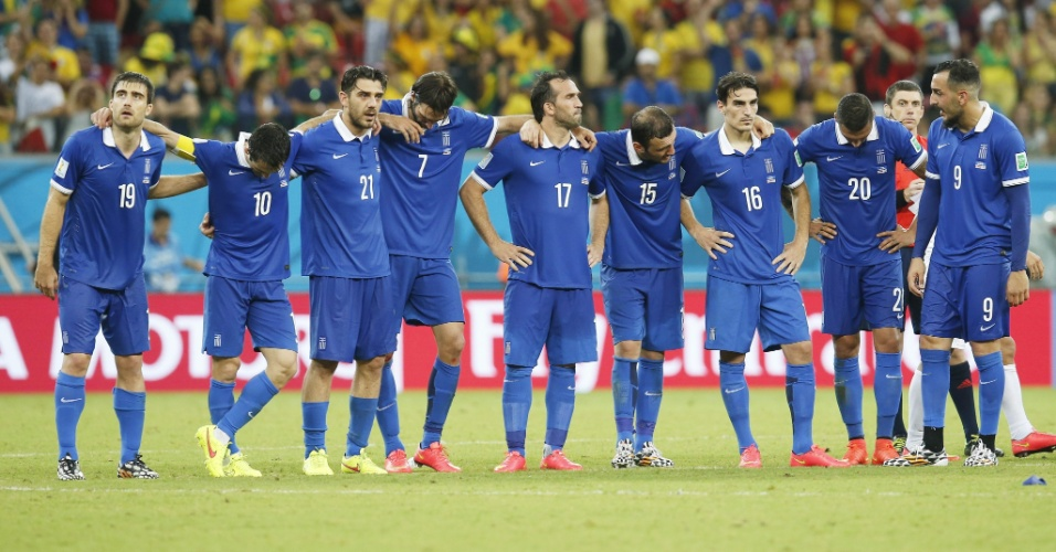 Jogadores da Grécia ficam abraçados no centro do gramado durante a disputa de pênaltis contra a Costa Rica