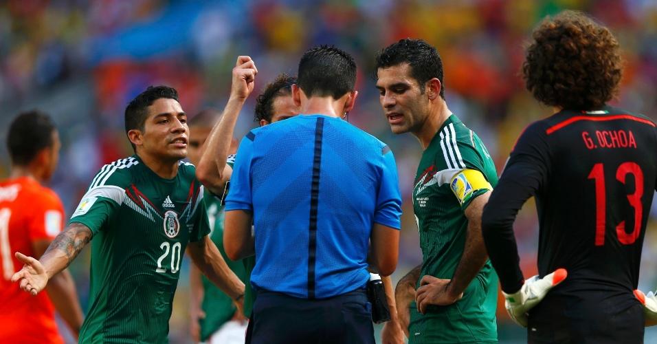 Jogadores do México reclamam com o árbitro após a marcação de um pênalti para a Holanda