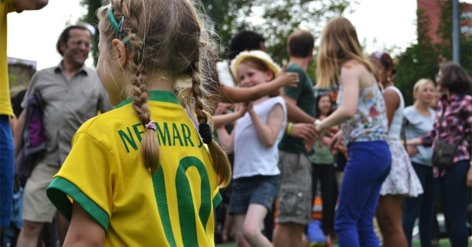 Pequena torcedora troca vestido de festa junina e chapéu de palha por camiseta do Brasil em festa junina realizada em Berlim, neste sábado