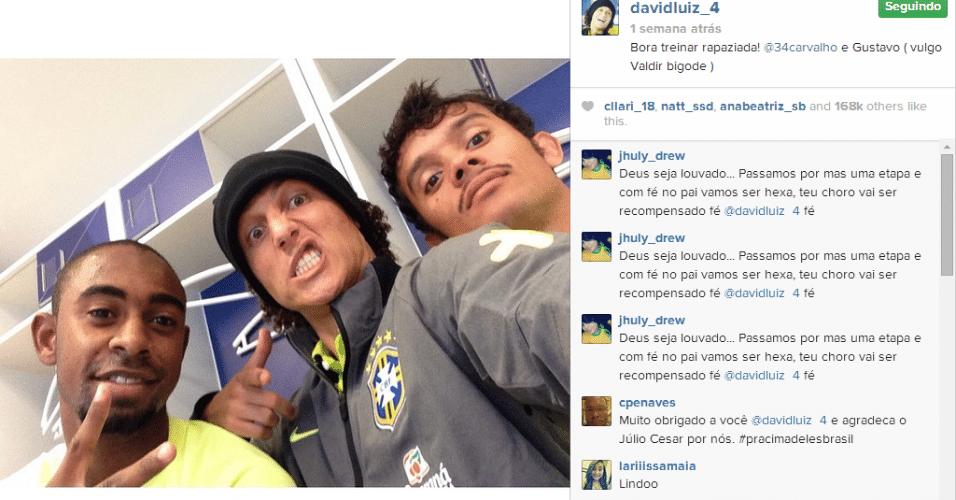 20.jun.2014 - David Luiz faz careta com jogadores da base do Fluminense que participam dos treinos da seleção brasileira na Granja Comary