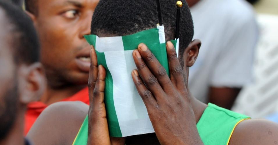 30.jun.2014 - Em Lagos, nigeriano se esconde atrás da bandeira nacional após eliminação da Copa do Mundo pela França