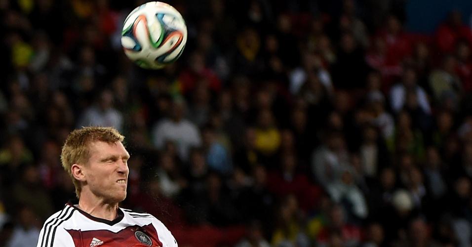 30.jun.2014 - Alemão Per Mertesacker faz careta para cabecear a bola e afastar o perigo contra a Argélia, no Beira-Rio