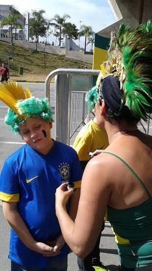 Artista Claudia Mattos pinta torcedores no Itaquerão antes de jogos da Copa do Mundo; na imagem garotinha é pintado com as cores do Brasil