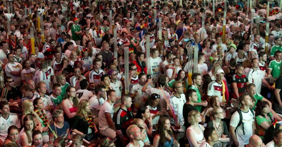 Em clube de Maiorca, na Espanha, turistas param para acompanhar partida entre Alemanha e Argélia em frente a telão