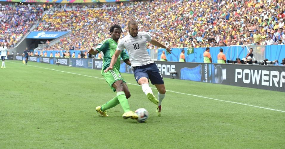 30.jun.2014 - John Obi Mikel, da Nigéria, marca de perto o francês Benzema durante a partida no Mané Garrincha
