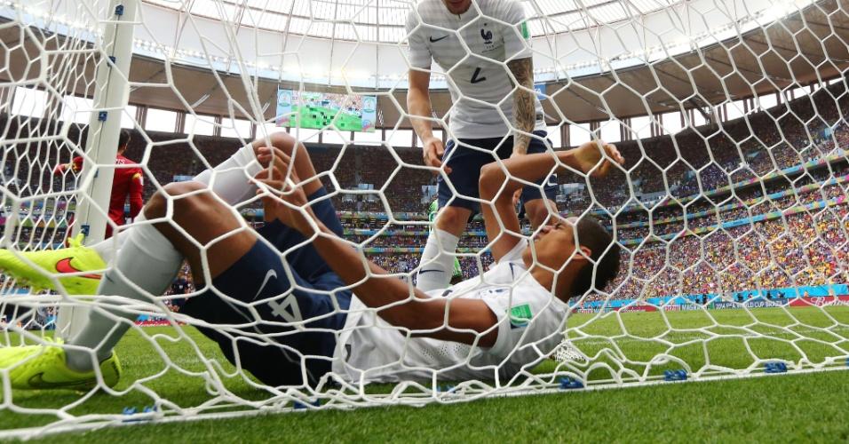 30.jun.2014 - Raphael Varane, da França, fica enroscado na rede do gol durante a partida contra a Nigéria, no Mané Garrincha