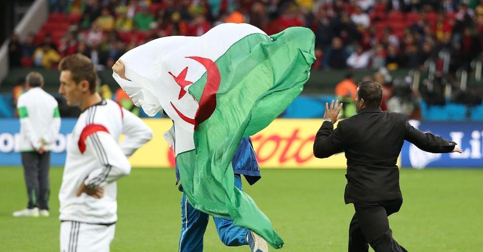 30.jun.2014 - Torcedor com a bandeira da Argélia invade o gramado durante o aquecimento do jogo contra a Alemanha, no Beira-Rio