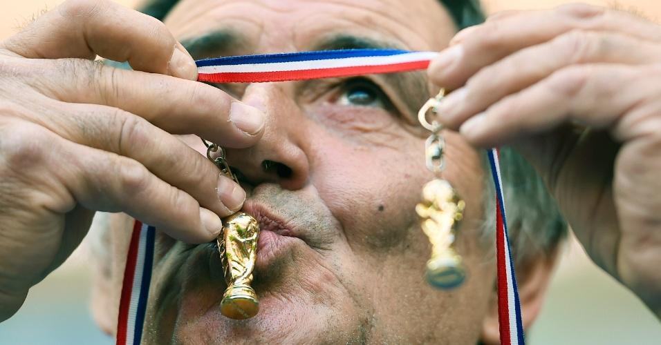 Torcedor francês beija chaveiros com miniaturas da taça da Copa do Mundo durante o jogo contra a Nigéria