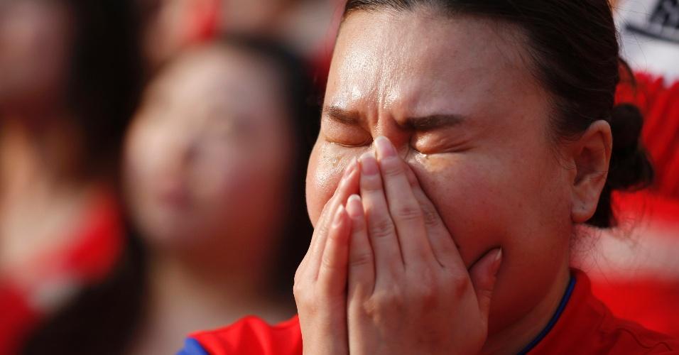 Torcedora sul-coreana chora após eliminação da seleção de seu país logo na primeira fase da Copa do Mundo