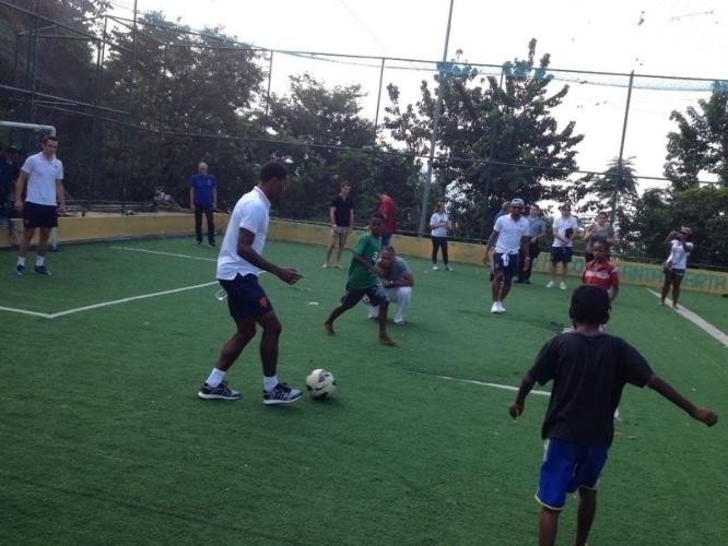 01.jul.2014 - Crianças da comunidade do Morro Dona Marta batem bola com jogadores da seleção holandesa