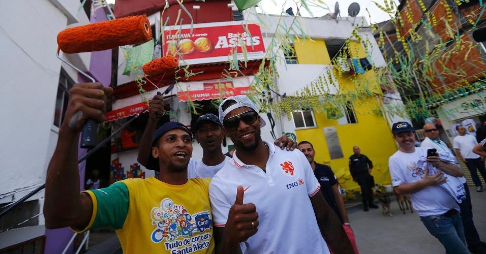 01.jul.2014 - Jeremain Lens mostra simpatia e posa para foto com trabalhador no Morro Dona Marta, no Rio de Janeiro