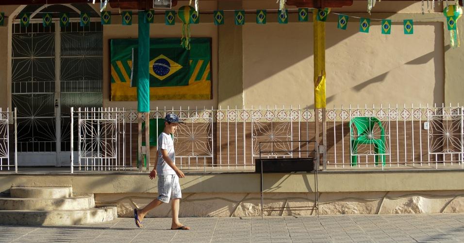Menino caminha na tarde pacata de Serra da Saudade. Praça principal foi enfeitada por ocasião da Copa do Mundo