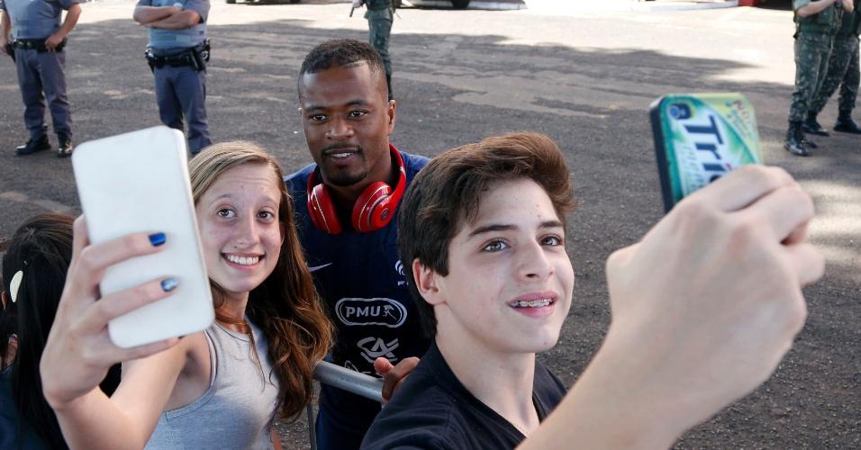 Patrice Evra atende alguns fãs e tira foto após treinamento da França em Ribeirão Preto