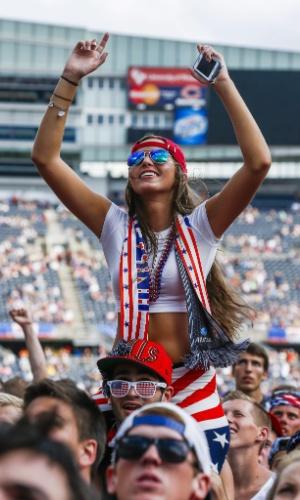 Torcedora sobe nas costas de outro americano para assistir ao jogo contra a Bélgica no Soldier Field, em Chicago