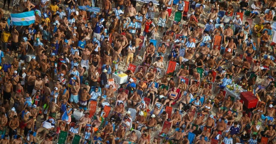 Torcedores em pé e sentados assistem ao jogo entre Argentina e Suíça no telão da Fan Fest de Copacabana