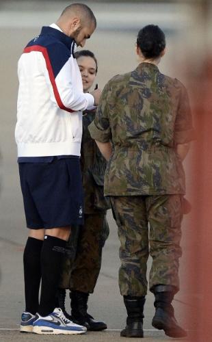 02.jul.2014 - Atacante francês Karim Benzema dá autógrafo a militares brasileiras antes de embarcar em voo para o Rio de Janeiro