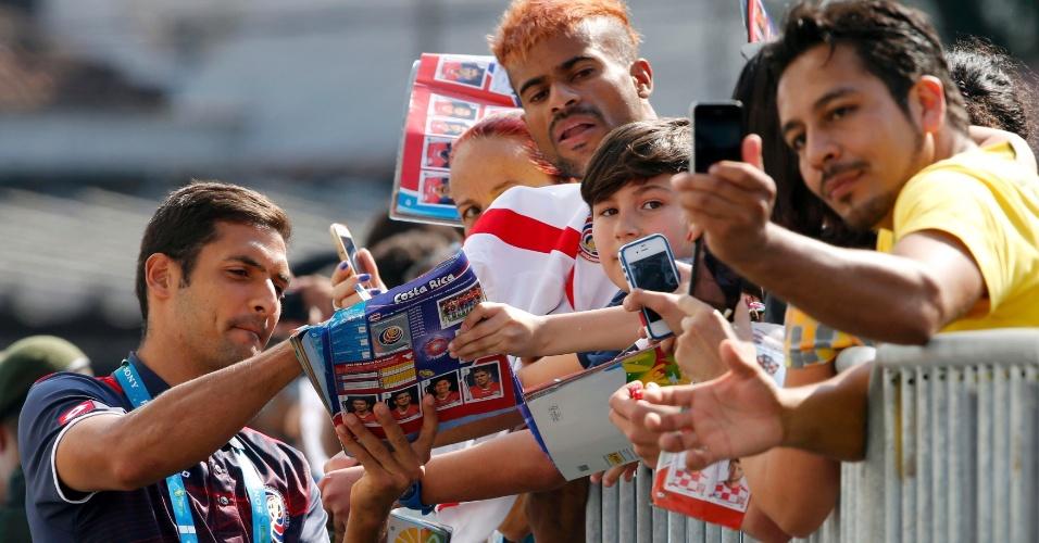 02.jul.2014 - Celso Borges, da Costa Rica, autografa álbum da Copa do Mundo de menino durante treinamento realizado em Santos