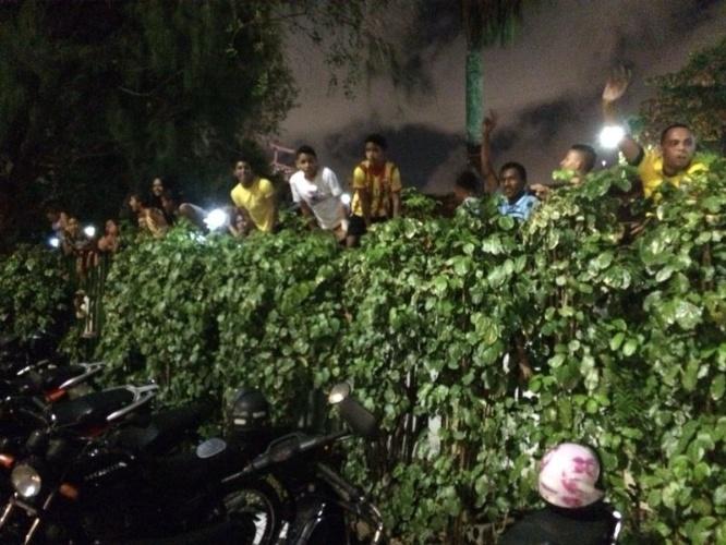 02.jul.2014 - Torcedores sobem mureta para verem chegada da seleção brasileira em hotel de Fortaleza