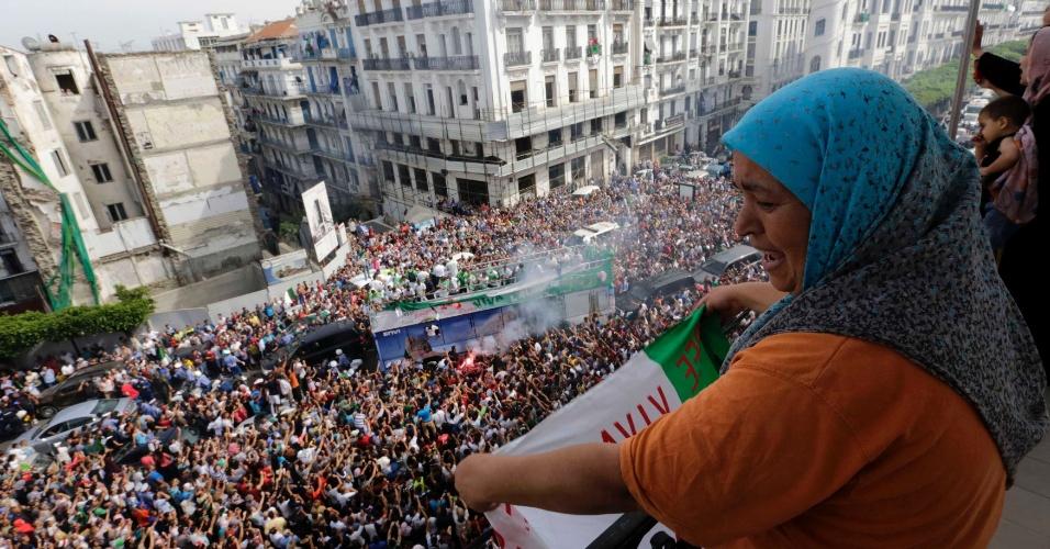02.jun.2014 - Mulher agita a bandeira a Argélia em desfile da seleção de futebol em carro aberto pelas ruas de Argel