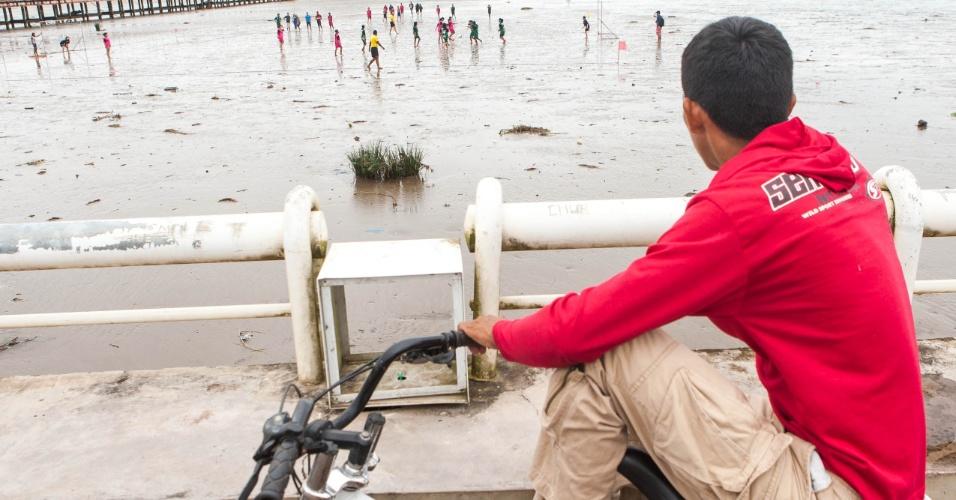 Ciclista observa a partida do futelama na orla do rio Amazonas