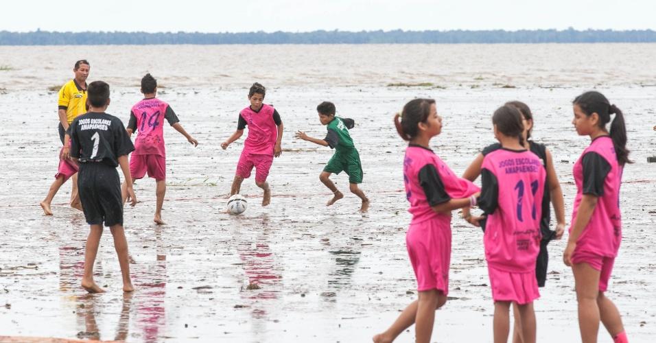 Crianças jogam o futelama na orla do rio Amazonas com a maré baixa