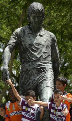 Crianças posam junto a estátua de Andres Escobar, zagueiro colombiano assassinado há 20 anos