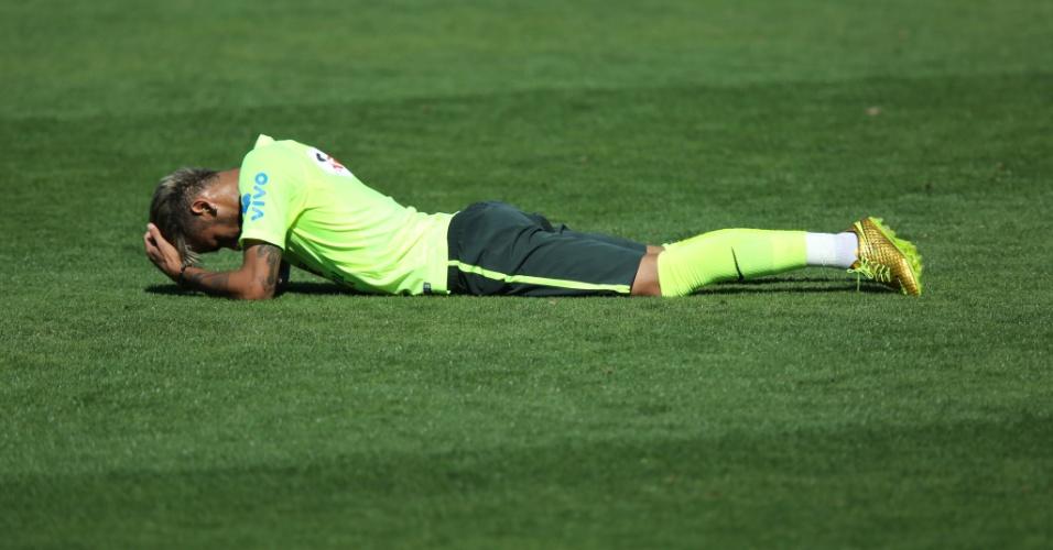 Neymar deita de bruços no gramado da Granja Comary durante treino da seleção brasileira