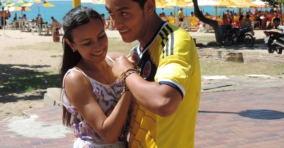 Colombiano Carlos Orosco tenta fazer passos de forró com brasileira na orla de Fortaleza