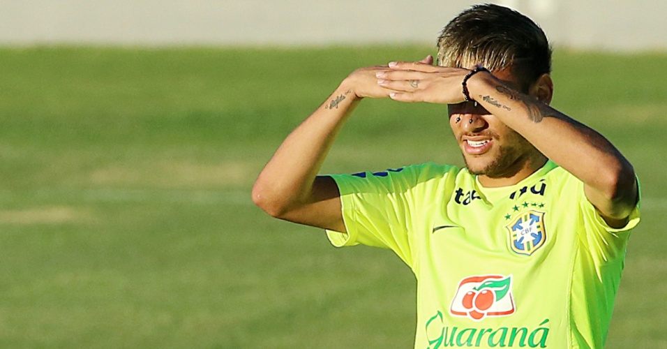 03.jul.2014 - Neymar usa as mãos para se proteger do forte sol de Fortaleza, durante treino no estádio Presidente Vargas