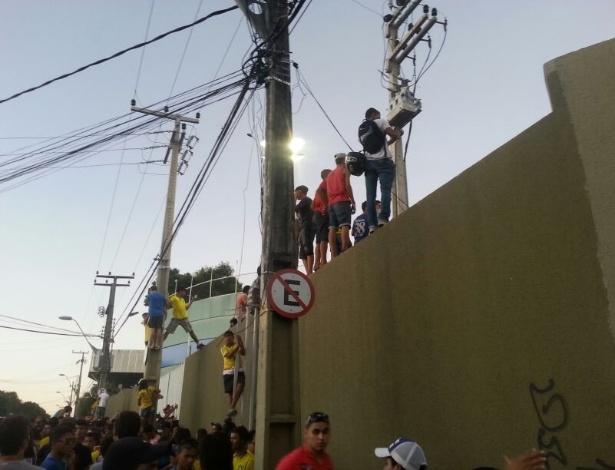 Torcedores sobem em muro para assistir à saída do ônibus da seleção brasileiro do Presidente Vargas