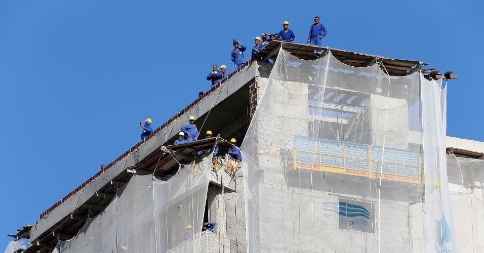 03.jul.2014 - Trabalhadores deram uma pausa na construção para observar a movimentação em Fortaleza, onde a seleção treina para a partida contra a Colômbia