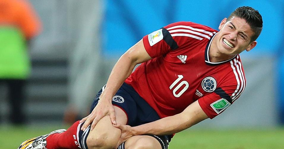 04.jul.2014 - Colombiano James Rodríguez fica caído no gramado após levar entrada do brasileiro Fernandinho, no Castelão