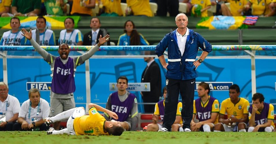 04.jul.2014 - Felipão faz cara de poucos amigos enquanto Oscar fica caído no gramado na vitória brasileira sobre a Colômbia por 2 a 1, no Castelão