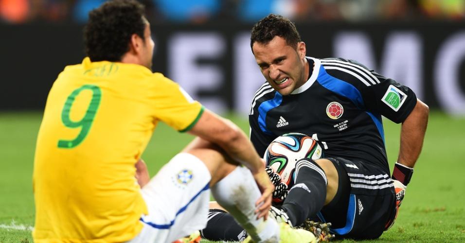 04.jul.2014 - Fred fica caído no gramado com o goleiro colombiano Ospina, após dividida na vitória brasileira por 2 a 1 no Castelão