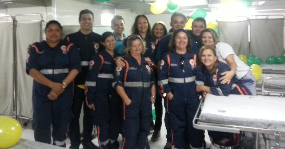 Funcionários do Posto Médico Avançado do Castelão reunido na enfermaria, com bexigas verde e amarelas enfeitando o ambiente
