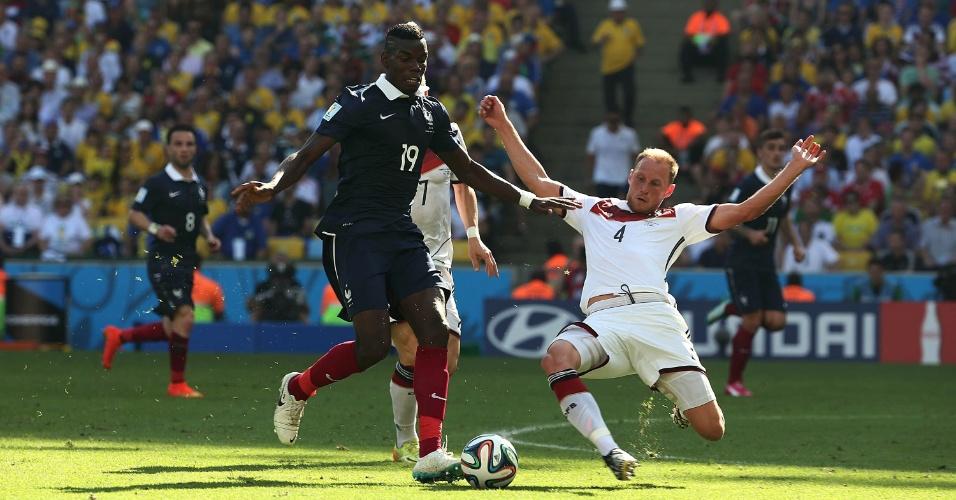 Pobga tenta drible sobre Howedes durante partida entre Alemanha e França