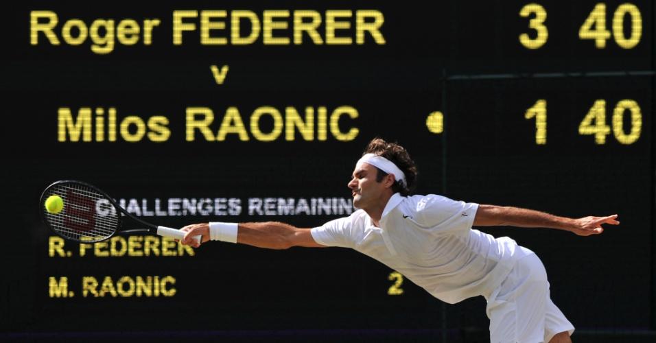 Roger Federer se estica para rebater bola para Raonic em Wimbledon