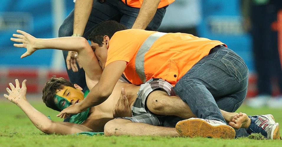 04.jul.2014 - Seguranças barram invasor que entrou no gramado do Castelão durante a vitória brasileira sobre a Colômbia por 2 a 1