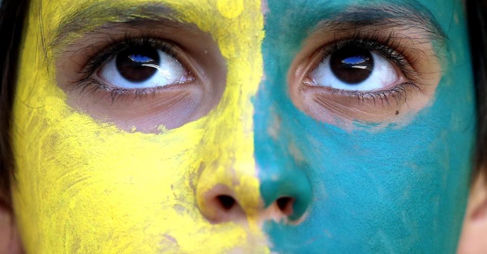 Torcedor com o rosto pintado de verde e amarelo aguarda o início da partida entre Brasil e Colômbia, pelas quartas de final da Copa