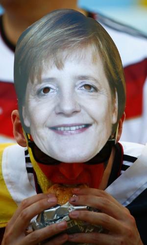 Torcedor come hambúrguer com a máscara da chanceler alemã Angela Merkel