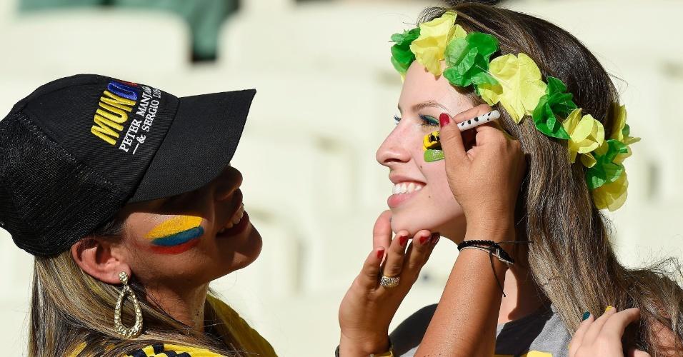 Torcedora colombiana pinta o rosto de colega brasileira no Castelão, antes do jogo entre Brasil e Colômbia