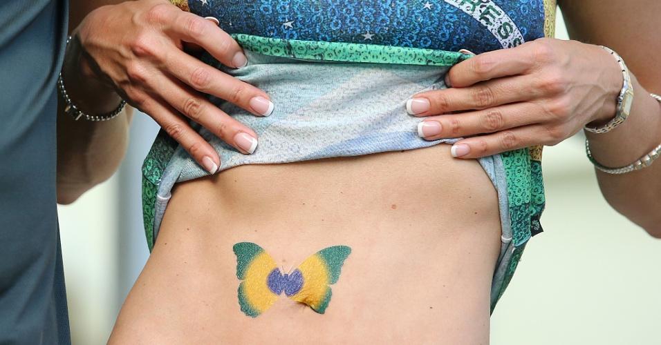 Torcedora mostra borboleta pintada com as cores do Brasil antes do jogo contra a Colômbia, no Castelão