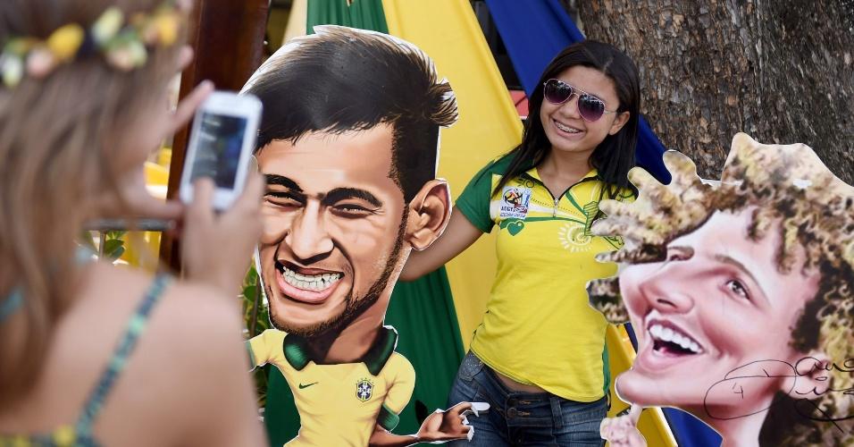 Torcedora posa com cartazes de Neymar e David Luiz antes da partida de quartas de final entre Brasil e Colômbia, no Castelão