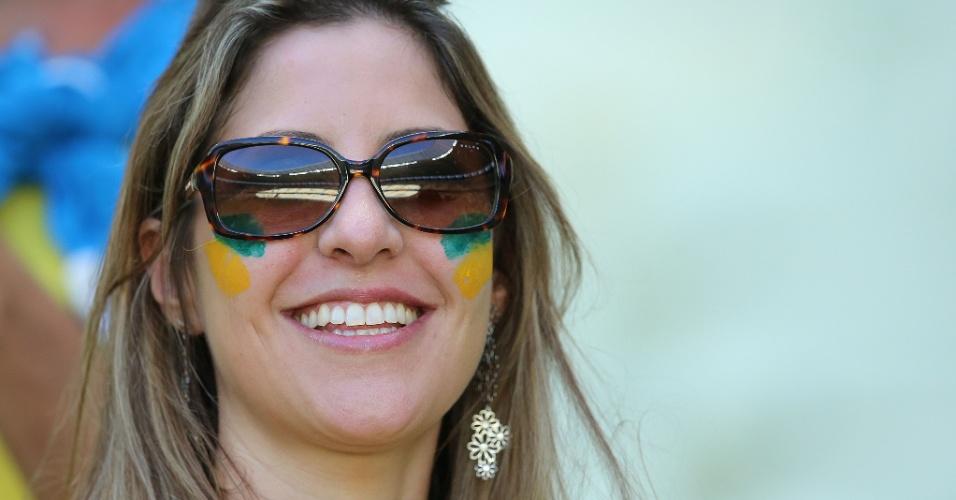 Torcedora sorri enquanto aguarda a partida de quartas de final da Copa, entre Brasil e Colômbia, no Castelão